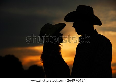 a young couple in love silhouette in cowboy hats - stock photo