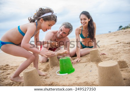 A young couple is playing at the beach with their daughter, a six year old is building a sand castle with her parents. Focus on the girl - stock photo