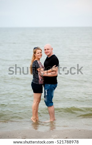 A young couple is walking in the sea