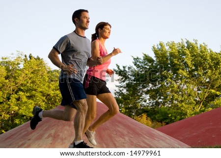 A young couple jog around a park with each other. - horizontally framed - stock photo