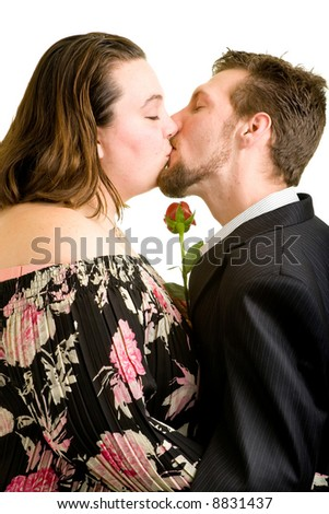 A young couple kissing while holding a single red rose.