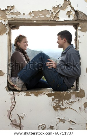 a young couple laughing together and having fun inside a window frame of an old building - stock photo