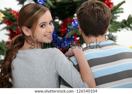 A young couple looking at a Christmas tree. - stock photo
