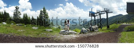 A young couple looks out over a panoramic view from Mount Mansfield in Vermont, USA.  - stock photo