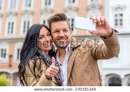 a young couple making a self portrait with a cell phone. selfies are in. - stock photo