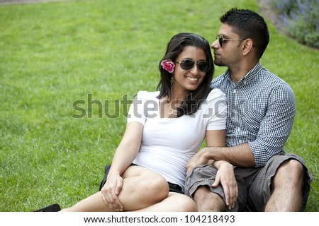 A young couple on a grass background.