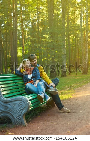 A young couple on a park bench - stock photo