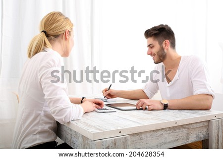 A young couple organizing their financial situation at home.