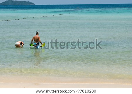 A young couple out scuba diving - stock photo