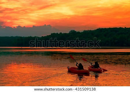 A young couple paddle kayaks on a lake at sunset.