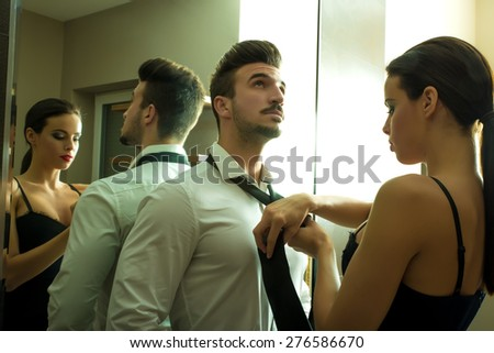 A young couple preparing to go out and getting ready and dressed in the changing room.  - stock photo