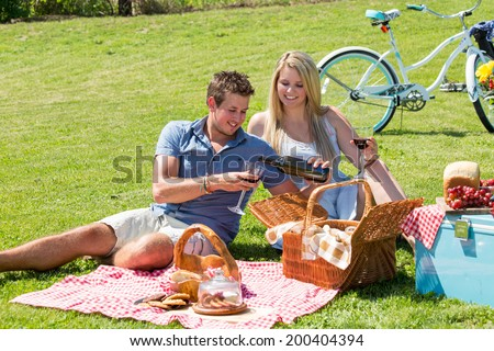 A young couple shares a happy moment picnicking on the grass in the countryside - stock photo