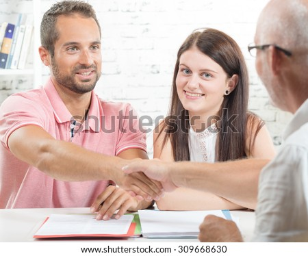 a young couple signs a contract - stock photo