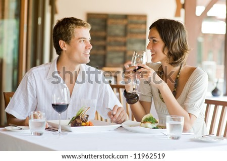 A young couple sitting at a table at an outdoor restaurant