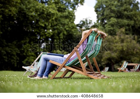 A young couple sitting on deckchairs in St James Park - stock photo
