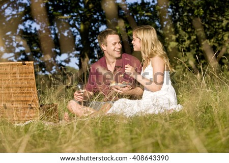 A young couple sitting on the grass, having a picnic - stock photo