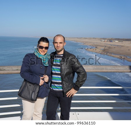 A young couple standing against a fence by the beach