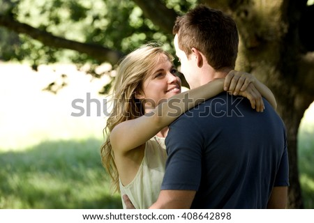 A young couple standing beneath a tree, embracing - stock photo
