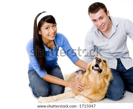 A young couple stroke their dog - shot in studio on white background