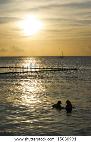 A Young couple swims in tropical waters at sunset