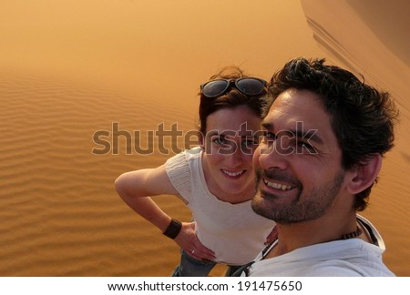 A young couple taking a self picture while climbing to the top of the Great Sand Dune in the red dune sea of Erg Chebbi, Morocco.  - stock photo