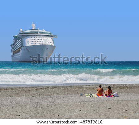 A young couple taking sun looking a big cruise ship moored on the beach. Copy space