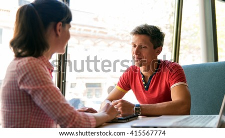 A young couple talking in the cafe - stock photo