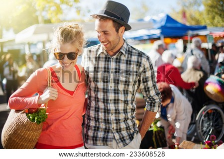 a young couple walking on a market on a sunny morning, the young woman carries a basket with fruit and vegetables - stock photo