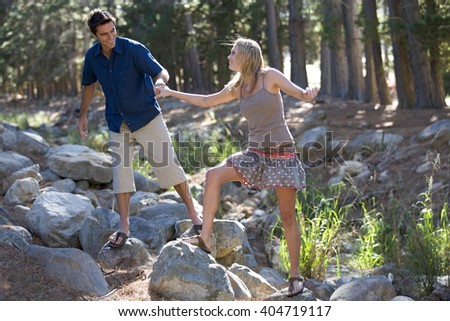 A young couple walking over rocks