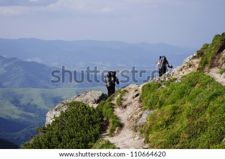 A young couple walks down the steep gradient on the background of mountain spaces - stock photo