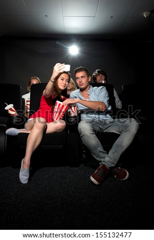 A young couple watching a movie at a cinema and photographing themselves with a Smartphone