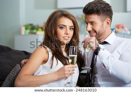 a young couple with champagne glasses celebrating  - stock photo