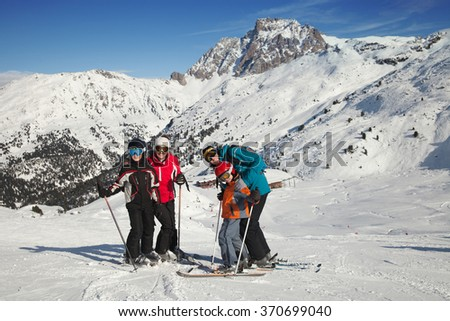 A young couple with two boys in a ski resort on a sunny day - stock photo