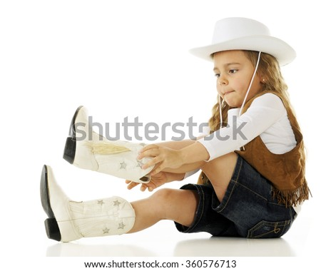 A young cowgirl concentrating as she puts on her boots.  On a white background.
