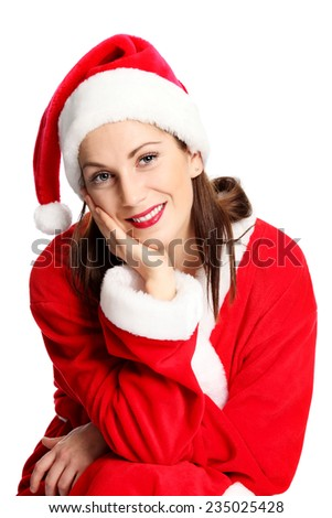 A young cute and attractive Mrs Santa Claus sitting down, wearing a red costume and hat. White background. - stock photo