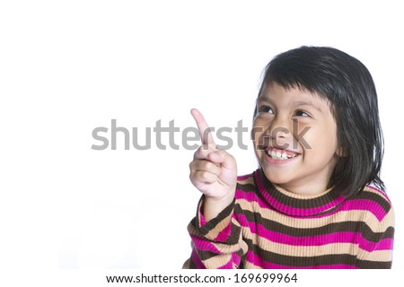 A young cute girl is pointing in the corner. She also looks there and smiles. Isolated over white.  - stock photo