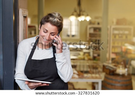A young deli employee talking on the phone while working on a tablet - stock photo
