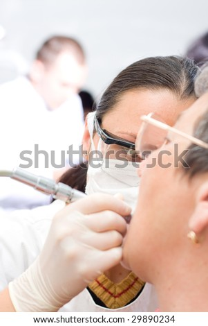 A young dentist treating an old woman's teeth whit the turbine, a blurred male doctor in the background - part of a series.
