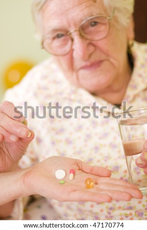 A young doctor giving medications - drugs and vitamins - and a glass of fresh water to an elderly woman - focus on pills. - stock photo