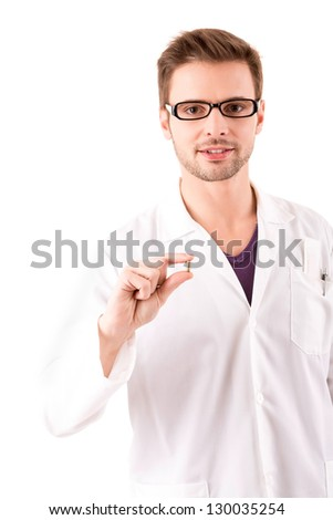 A young doctor holding some pills, isolated over white - stock photo