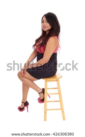 A young East Indian woman sitting in profile on a chair, smiling into the