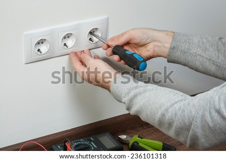 A young electrician installing an electrical plug in a new house. - stock photo