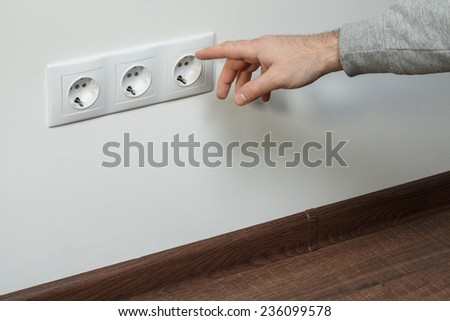 A young electrician shows a finger an electrical plug in a new house. - stock photo