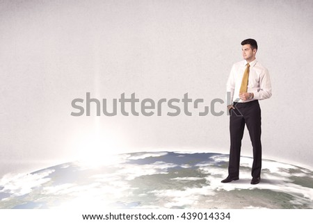 A young elegant office worker standing on top of a drawn world globe while celebrating his successful career concept. - stock photo
