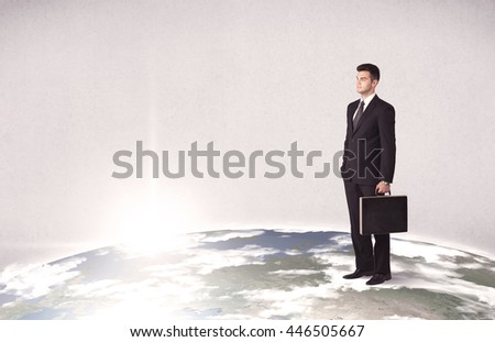 A young elegant office worker standing on top of a drawn world globe while celebrating his successful career concept.