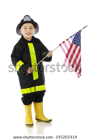 """A young elementary """"fire chief"""" happily carrying an American flag.  On a white background. - stock photo"""
