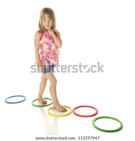 A young elementary girl walking a path of colorful rings.  On a white background.