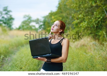 a young emotional girl with laptop in the Park