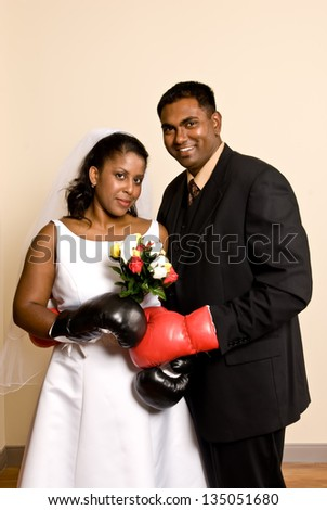 A young ethnic couple wedding attire wearing boxing gloves. - stock photo