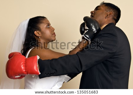 A young ethnic couple wedding attire wearing boxing gloves. She connects with a right hook, showing her husband who's boss.